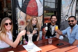 Two women and two men sit at an outdoor table beside a graffiti wall and hold up their drinks while smiling at the camera.