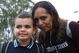 Deborah Lonsdale smiles and leans down to pose with young son Cameron