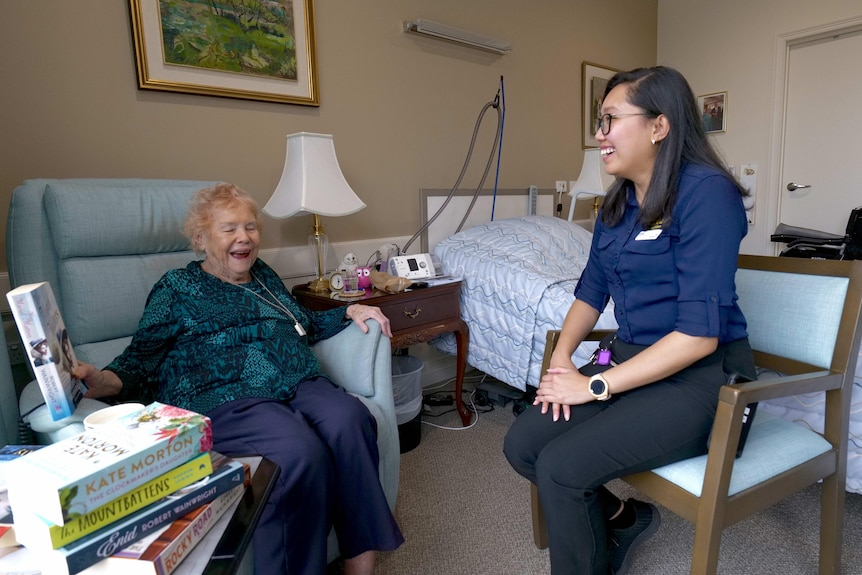 A 93-year-old woman and a younger nurse smiling and laughing in an aged care facility room.