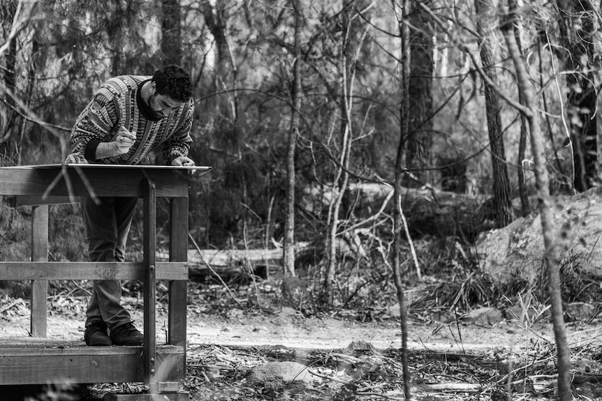 Young man leaning on the rail of a timber lookout writing on a placard