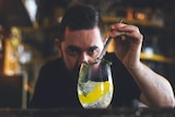 Sean Baxter uses tweezers to add a garnish to a gin and tonic.