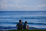 Two people sit on a hill overlooking the ocean at Burleigh Heads.