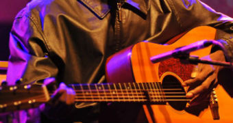 A close up of Dr G Yunupingu's hands on his guitar as he performs in London.