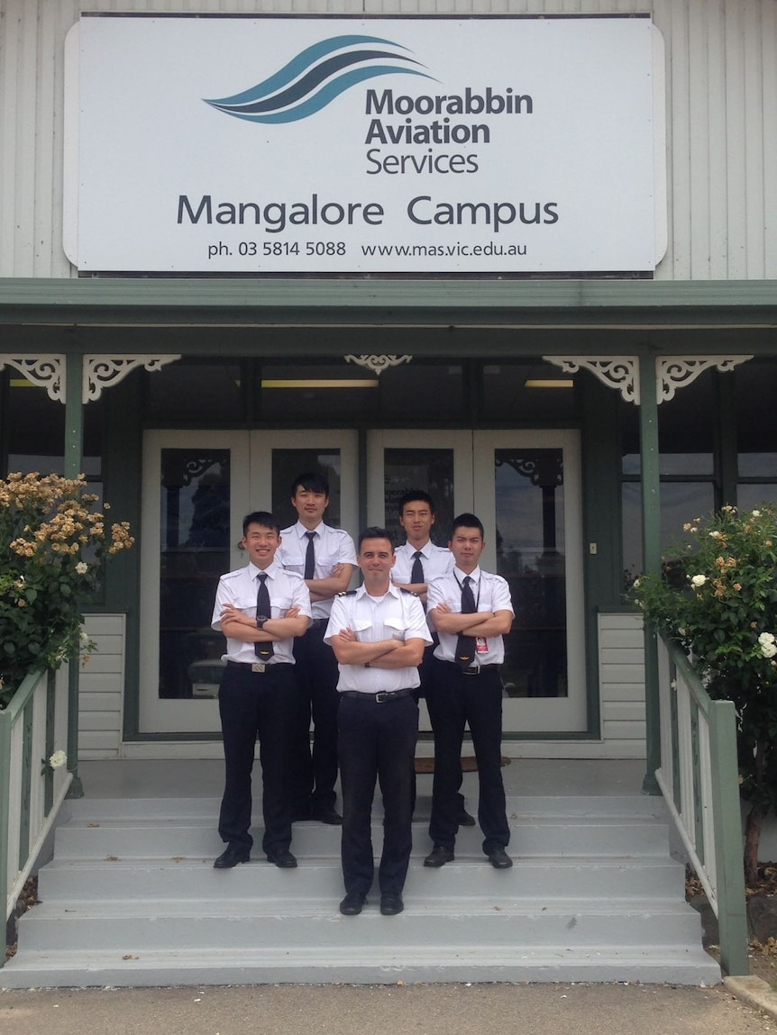 Four pilots standing with arms crossed outside the Mangarlore pilot training school