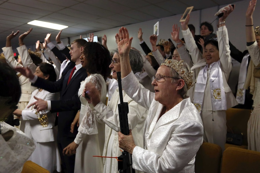 A woman wears a crown and holds an unloaded weapon as she and other church worshippers cheer