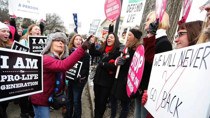 反堕胎抗议者(左)在美国最高法院前与堕胎维权人士(右)争论。