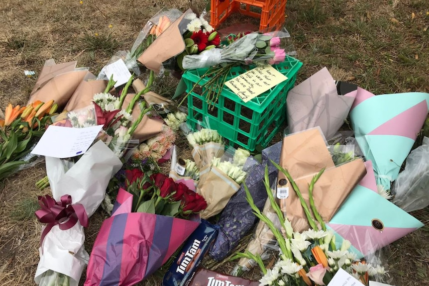 Bunches of flowers, cards and chocolate biscuit packets are laid out on a patch of grass.
