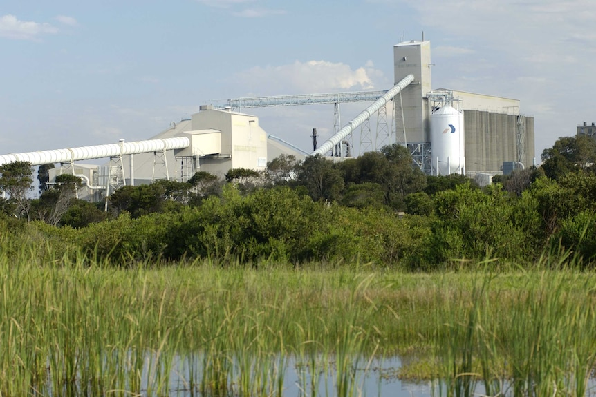 A factory with a pond and green grass in the foreground.