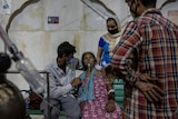 A man cradles a woman who is receiving oxygen while another man and woman watch on.