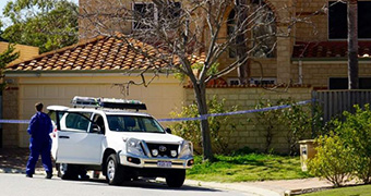 A police car in front of a big house roped off by crime tape.