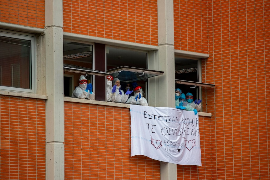 Health workers pictured applauding inside an open window  during a memorial for their co-workers in Spain.