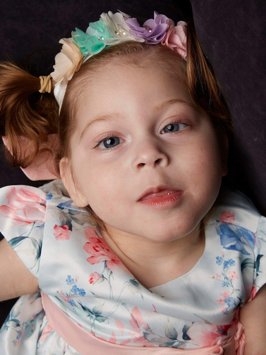 Portrait of Tahlea, two-and-a-half-years old, she has pigtails and wears a rainbow flower headband and a floral dress.
