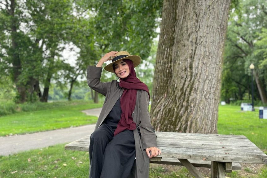 A woman wearing a headscarf and hat sits on a table in a park