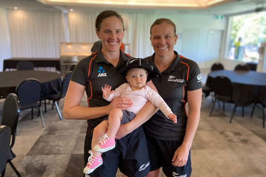 Two female cricketers smile at the camera, with one holding a baby in her arms.