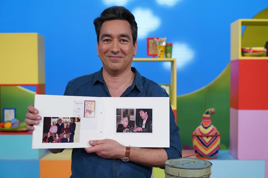 Play School presenter Alex Papps holding a scrapbook he made about his grandma to depict talking about death and grief with kids
