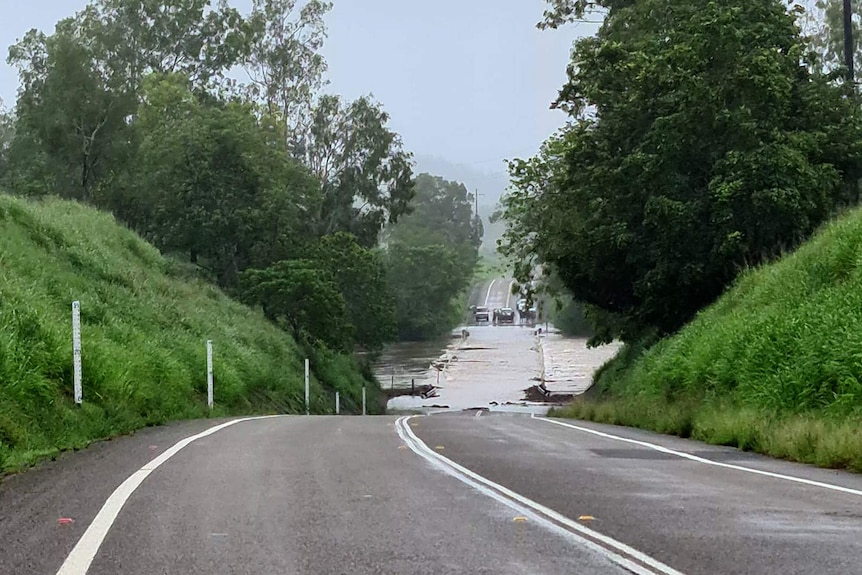 Several cars wait on the other side of Abergowrie Bridge over the Herbert River which is flooded