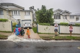 A family plays in the rain outside a home from ex-cyclone Debbie in Newmarket.