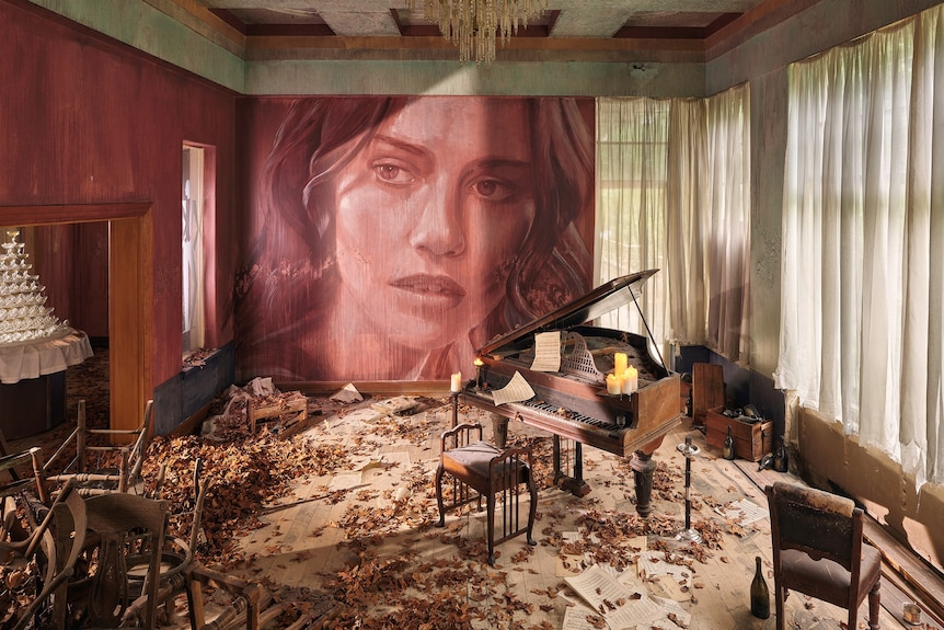 Piano room in decaying mansion with portrait of woman on wall