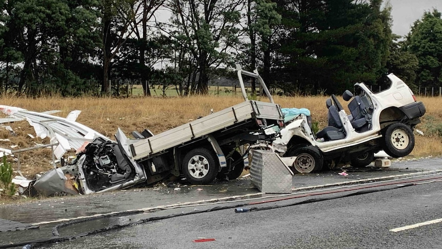 Two heavily damaged cars - a ute and a four-wheel drive - are crashed off the side of a highway
