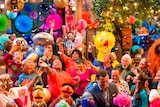 A group shot of the Sesame Street show set shows the cast looking up at confetti and balloons.