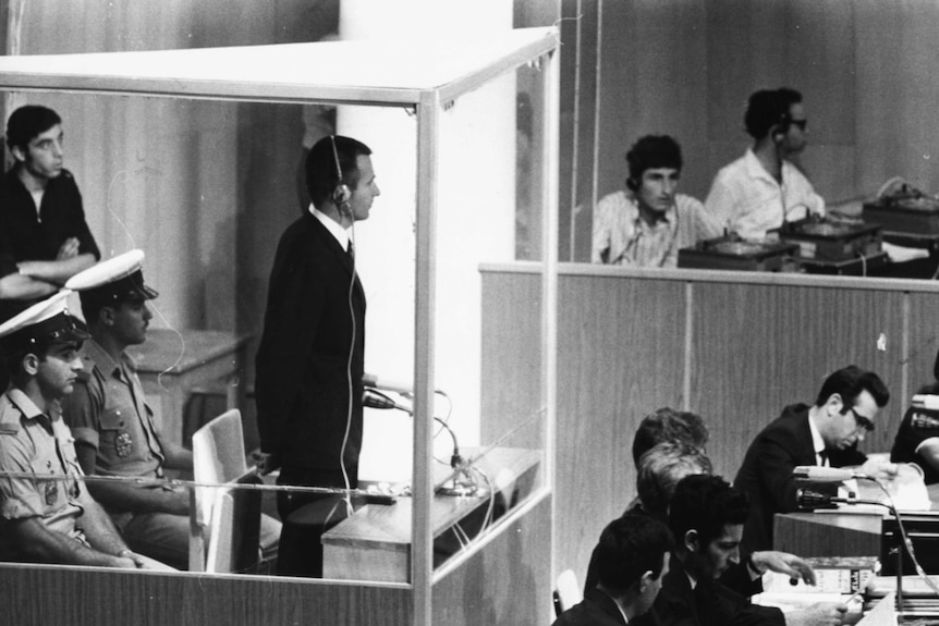 Denis stands in a box guarded by police in an active court room