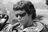 A black and white image of Lou Reed sitting on a bench wearing sunglasses as he plays guitar