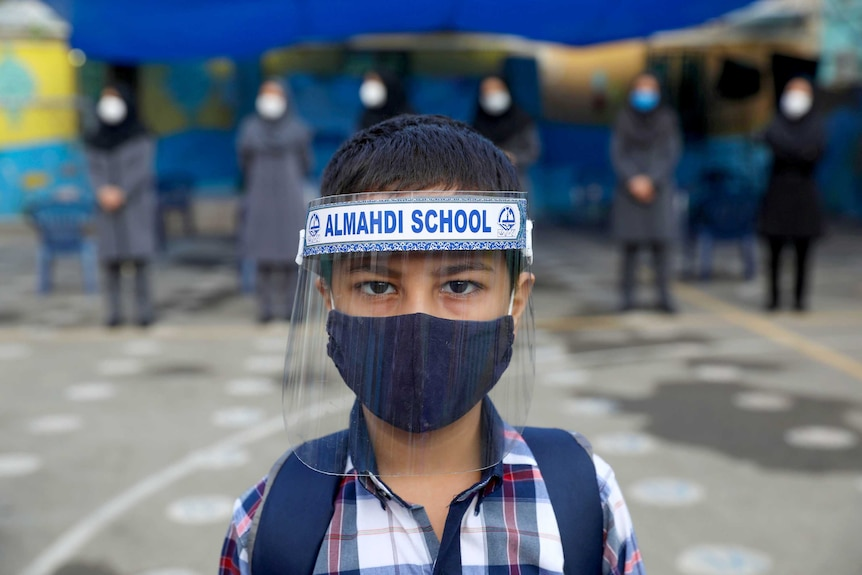 A little boy in a face mask and face shield