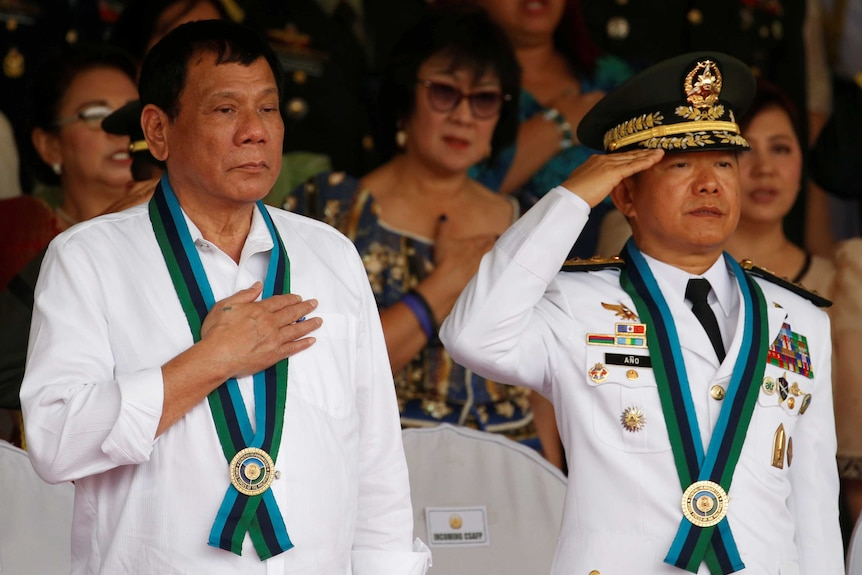 Philippine President Rodrigo Duterte stands to attention next to Armed Forces chief General Eduardo Ano.