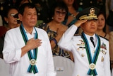 Philippine President Rodrigo Duterte stands to attention next to Armed Forces chief of staff General Eduardo Ano.