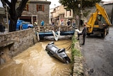 Car being hoisted out of a river following flash flooding