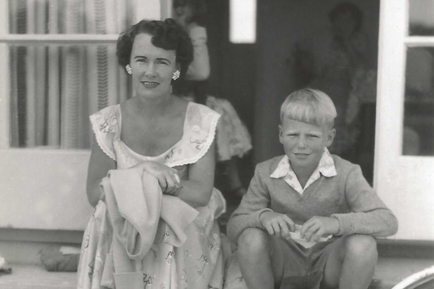 A black-and-white photo of a mother and her child sitting on the front porch of a house, circa 1960s.