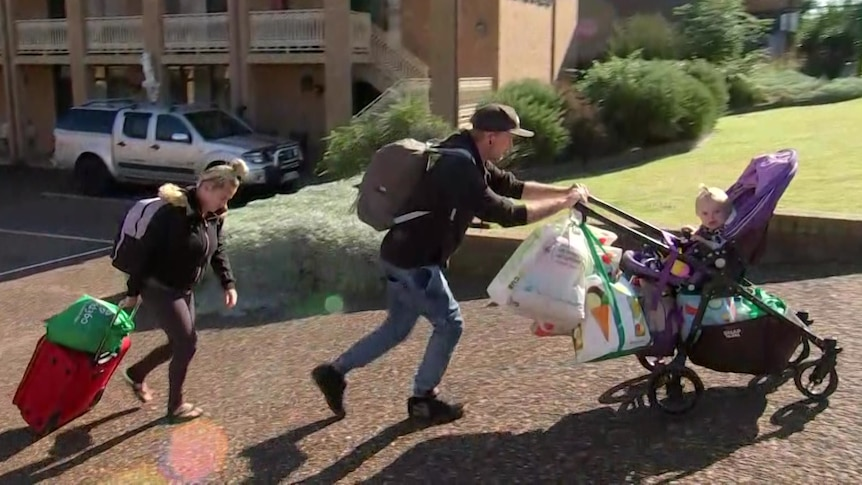 Homeless family with stroller and carrying bags.