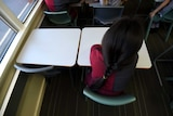 An unidentified child sits alone at a desk in a primary school classroom
