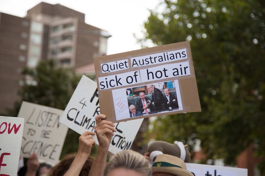 A hand holds up a placard at a demonstration reading: Quiet Australians sick of hot air
