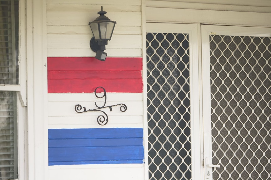 A close up of the red, white and blue stripes painted on Shannon Yates' house