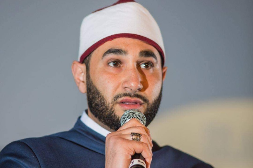 A close up of Sheikh Alaa speaking into a microphone.