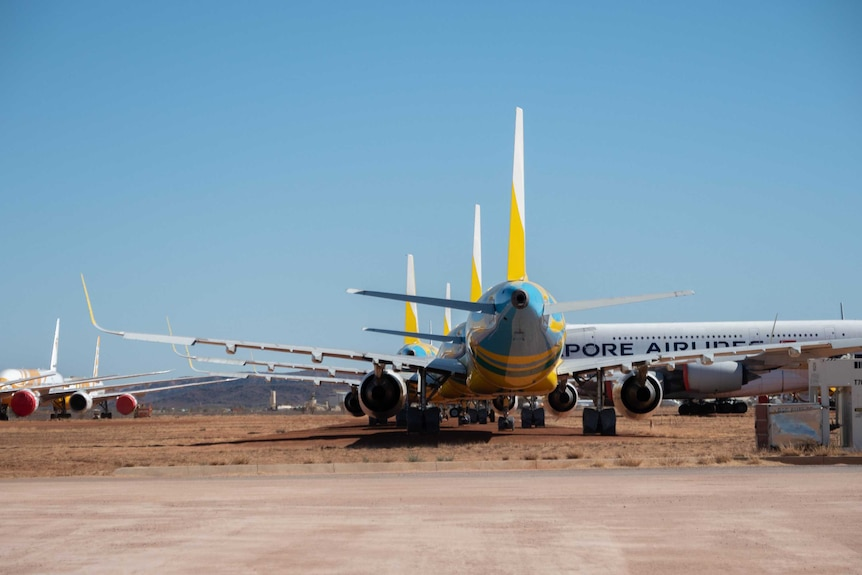 Large planes with different logos sit at Alice Springs airport facility.