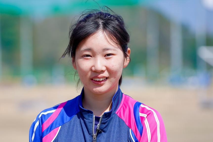 A young Japanese teen in a purple and pink athletic jacket