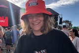A teenager at a music concert smiling at the camera.