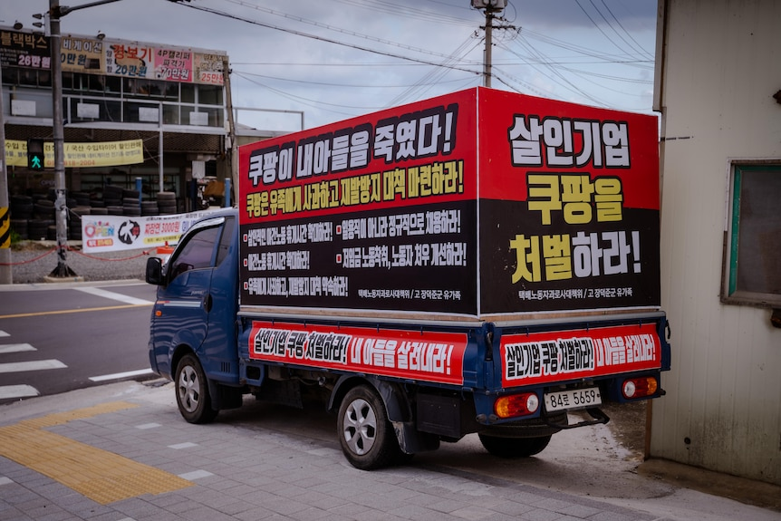 """A van with the words """"Coupang killed my son"""" on it."""