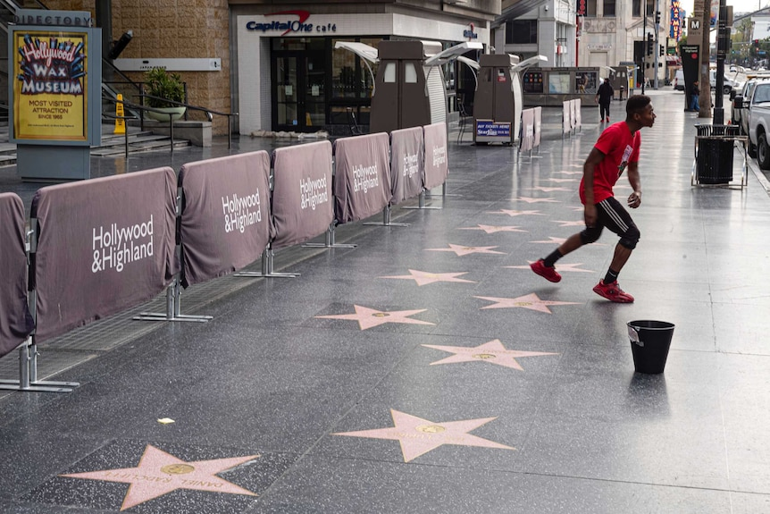 A man dances on an empty street that is usually teeming with people but is empty due to coronavirus fears.