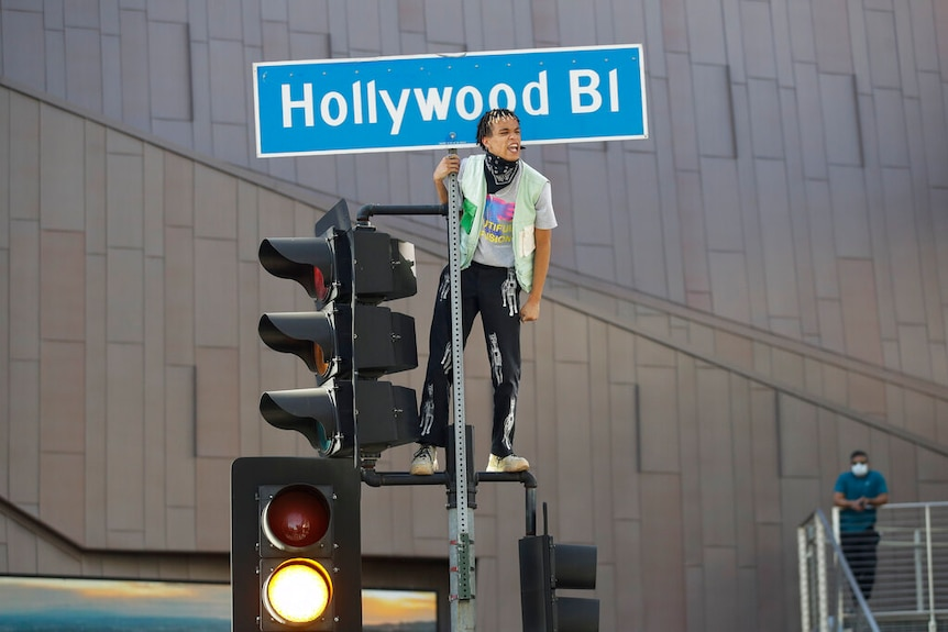 You view a man standing atop traffic lights as he holds onto a street sign that reads 'Hollywood Bl'.