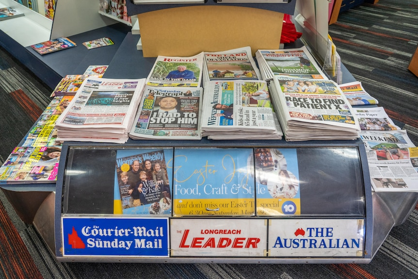 Stacks of newspapers sit on a display in a newsagency.