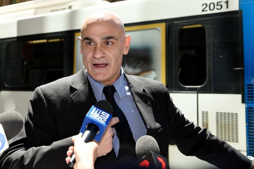 A man speaks in front of media microphones.