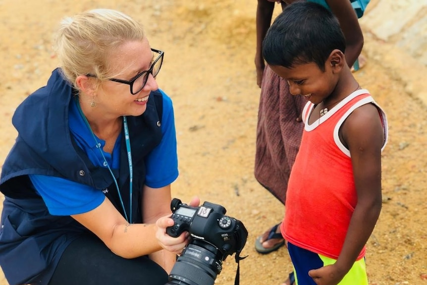 A western woman kneels down next to a young Burmese boy and shows him photographs in her camera.