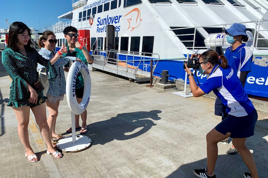Chinese tourists being photographed alongside a reef tour boat