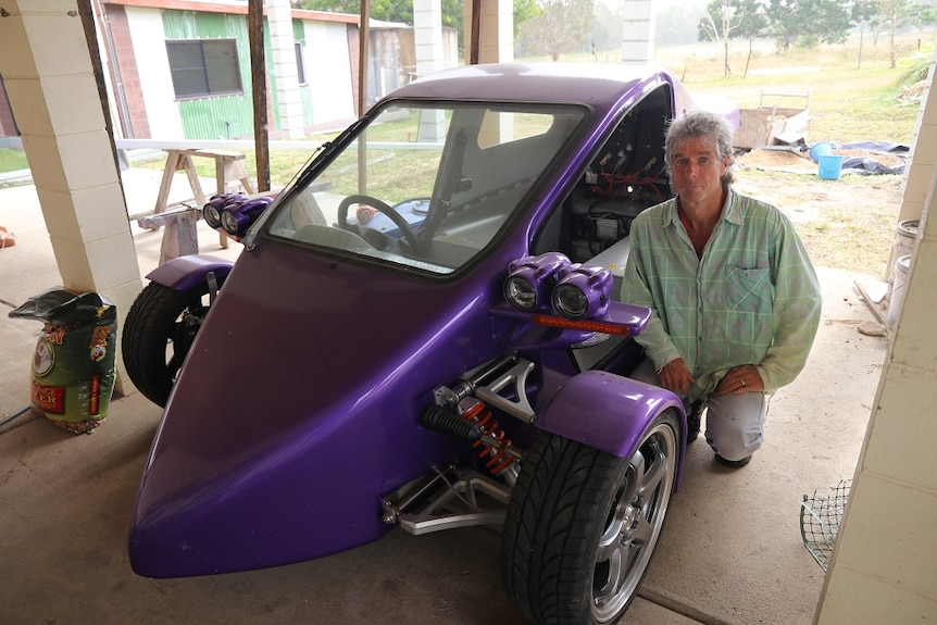 A man crouches next to a purple three-wheeled car/motorcycle