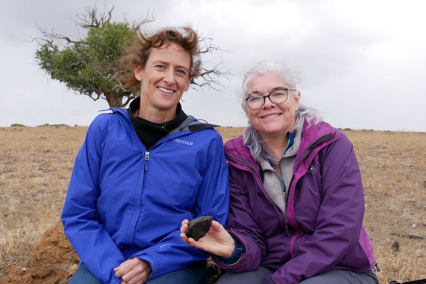 Two women outside looking windswept hold a small chunk of rock.