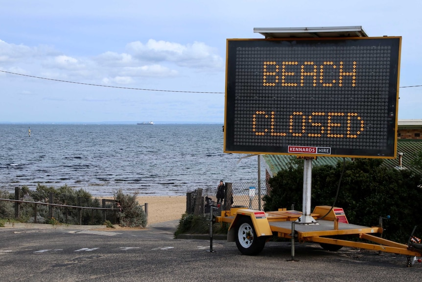 A large electric sign on concrete in front of a beach with a woman on the sand says beach closed.