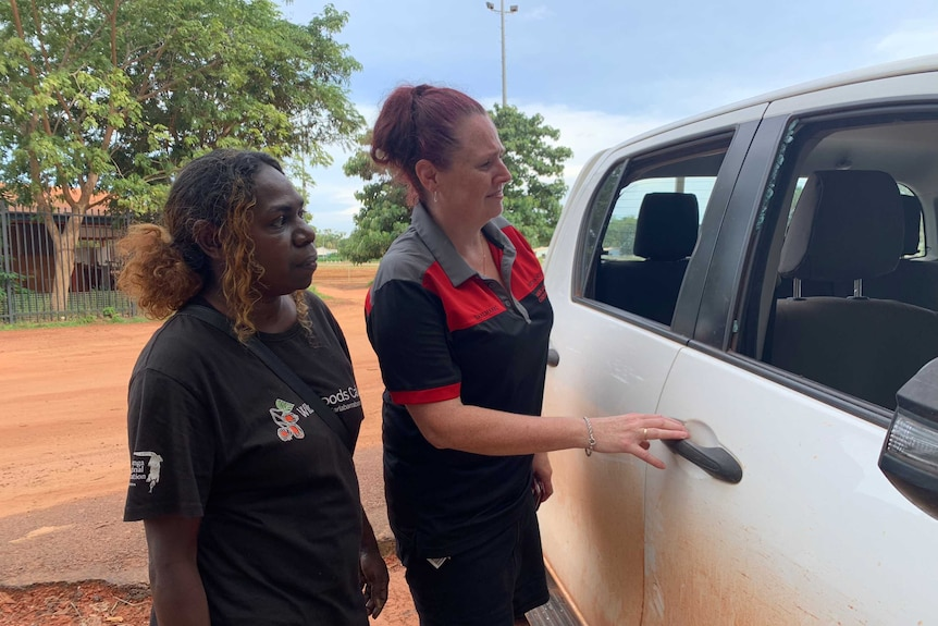 Two women in Bawinanga Aboriginal Corporation t-shirt and polo shirt inspect broken windows on the side of a ute.
